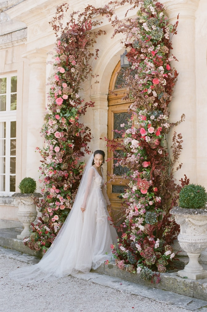 A black bride in her blush Inbal Dror wedding gown standing under her flower arch at Chateau Martinay