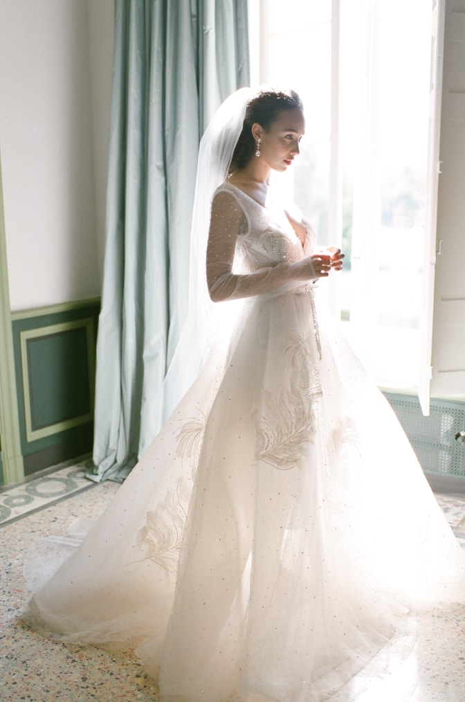 Black bride getting ready into her blush Inbal Dror wedding dress at Chateau Martinay in Provence