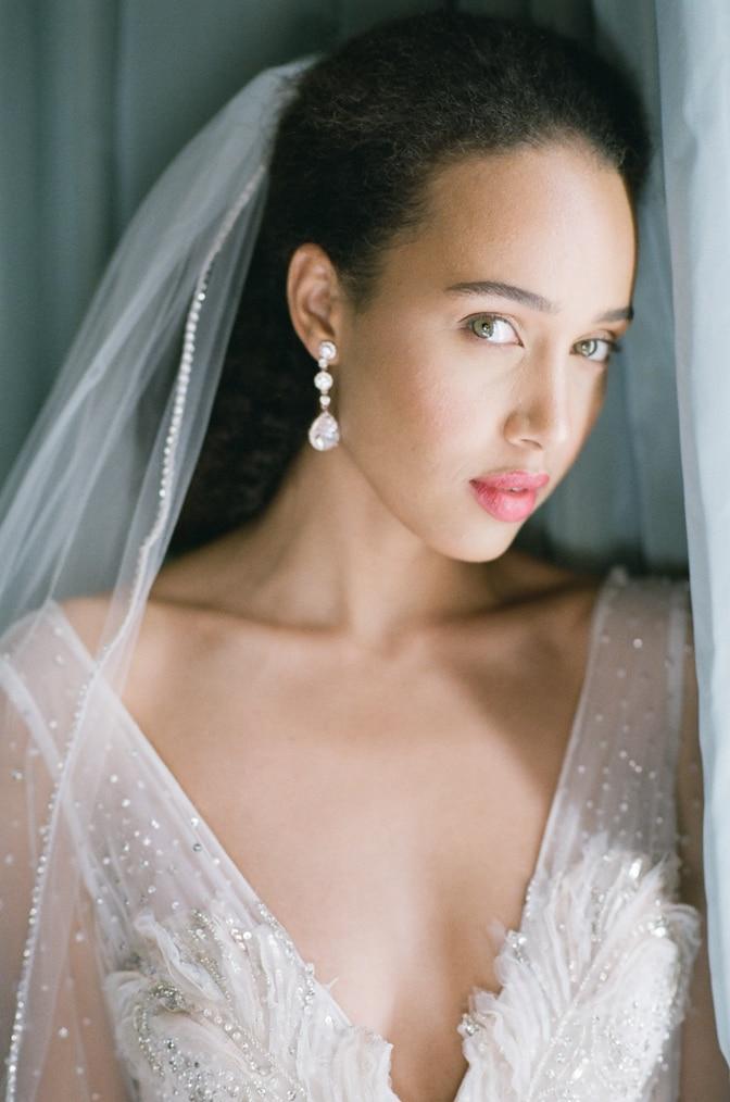 Closeup of a black bride in her blush Inbal Dror wedding dress standing next to the window