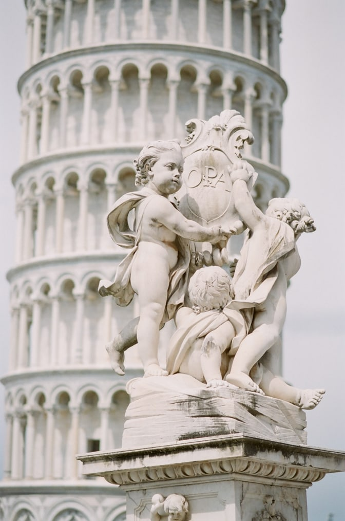 Closeup of baby statues in front of the Leaning Tower in Pisa Italy