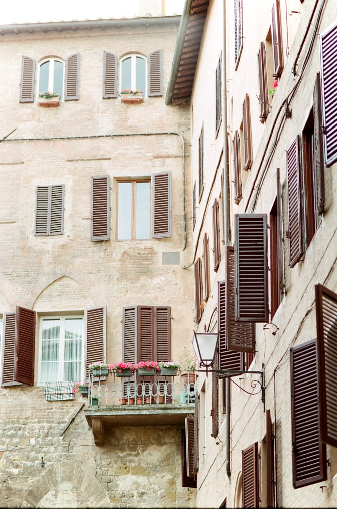 Beige-colored building in Siena with its brown window shutters in Siena Italy