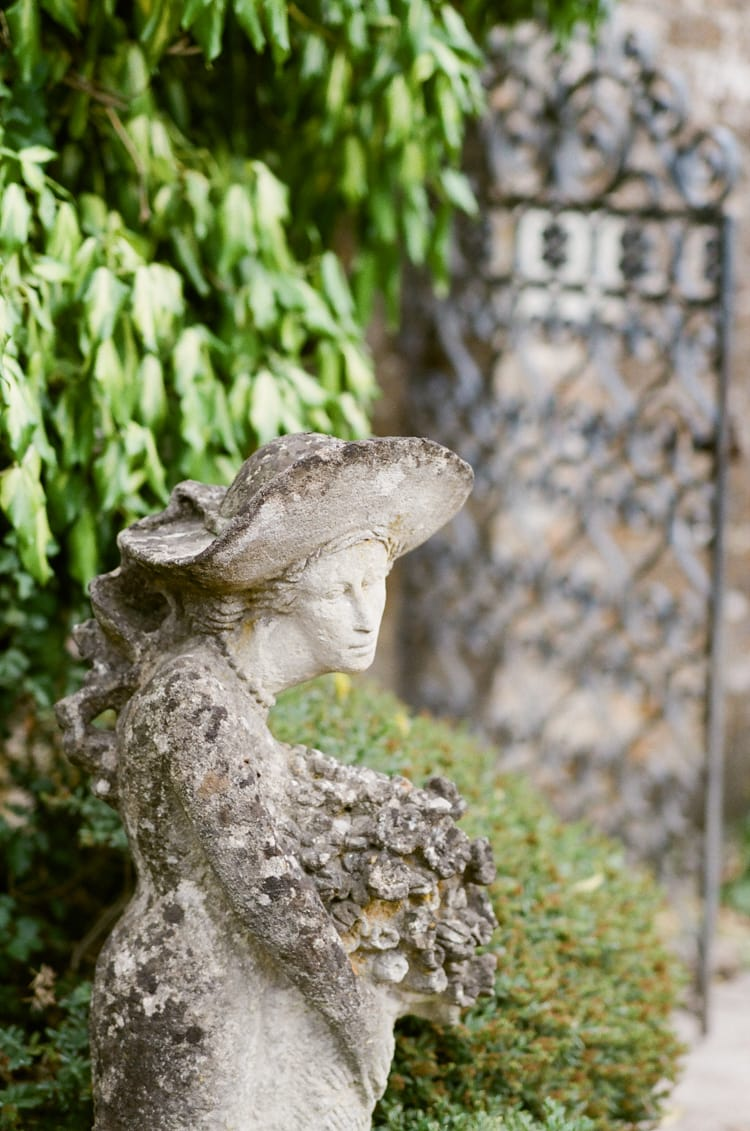 Closeup of a statue with hat at the Barnsley House gardens in the Cotswolds in England