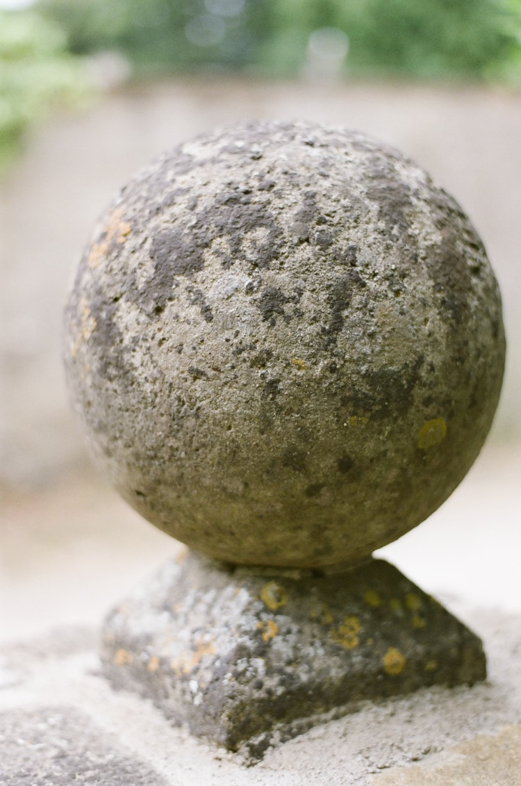 Closeup of a stone ball at the gate of the Barnsley House in the Cotswolds in England