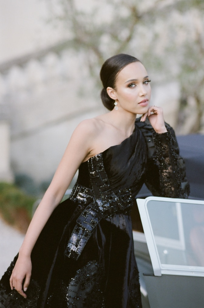 Black bride in her black Ziad Nakad gown leaning on a grey Royce Rolls and facing the camera