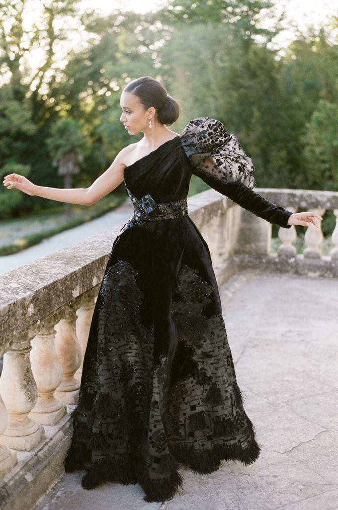 Black bride in her black Ziad Nakad wedding dress dancing on the terrace of Chateau Martinay in Provence