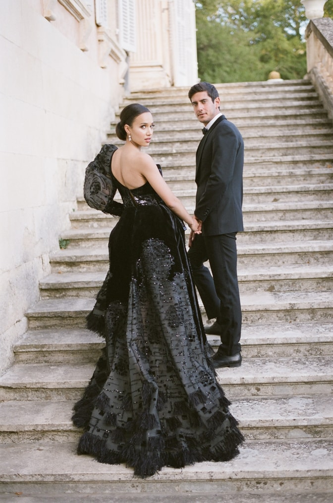 Bride and groom standing on the stairs of Chateau Martinay in Provence looking back into the camera