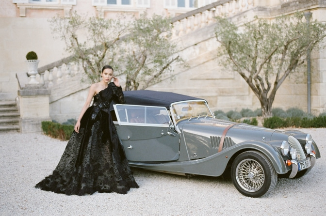 Black bride in black Ziad Nakad couture gown leaning on grey Royce Rolls at Chateau Martinay in Provence