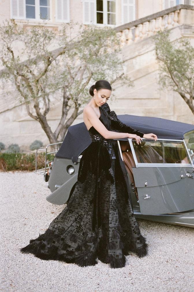 Black bride in her black Ziad Nakad couture gown opening the door of a grey Rolls Royce