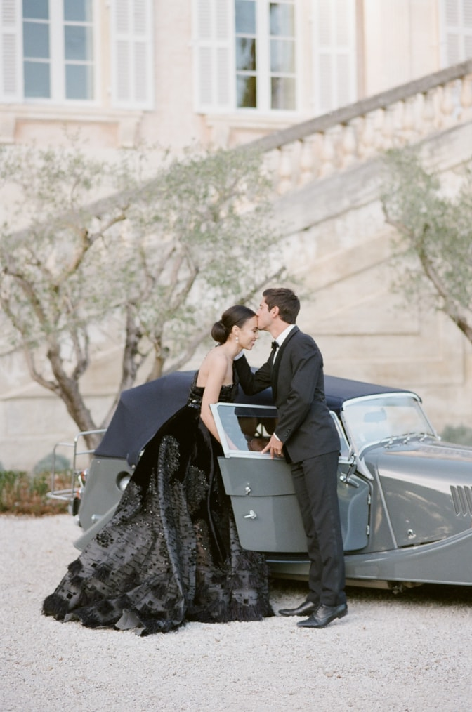 Groom kissing his black bride in front of a grey Royce Rolls at Chateau Martinay in Provence France