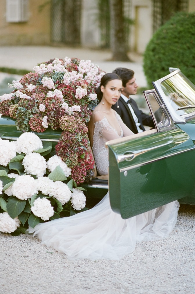 Black bride in her blush Berta Bridal gown sitting in a green car with door open