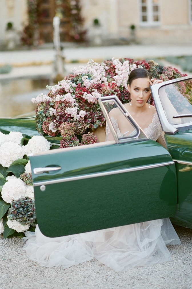 Black bride in her blush Berta wedding gown sitting in a green car filled with colorful hydrangea with door open