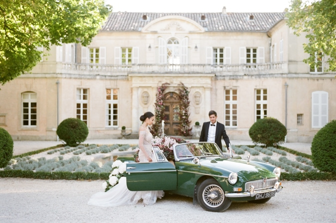 Bride and groom entering a green car filled with hydrangea in front of Chateau Martinay Provence