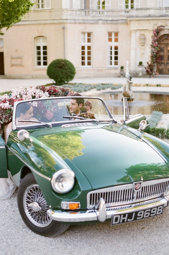 Bride and groom sitting in a green car filled with flowers and about to exit Chateau Martinay in Provence