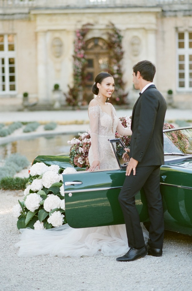 Bride and groom smiling at each other in front of a green car filled with colorful hydrangea