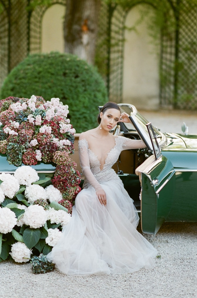 Black bride in her blush Berta Bridal gown sitting in a green car filled with colorful hydrangea with door open and looking into the camera