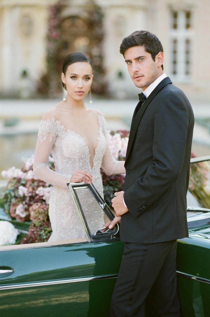 Bride and groom standing in front of a green car filled with hydrangea and looking into the camera at Chateau Martinay Provence