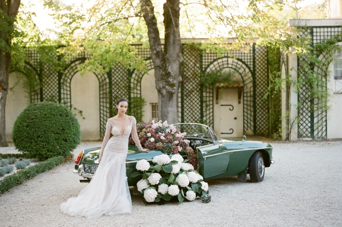 Planning your grand exit for your own wedding day in a green car filled with hydrangea