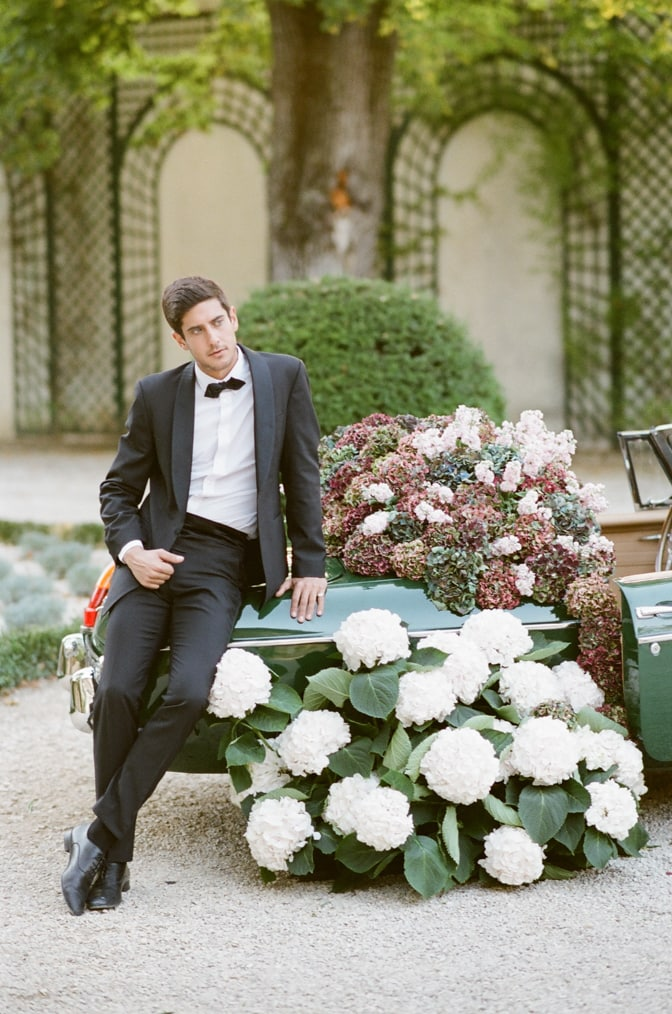 Groom sitting on the rear of a green car filled with colorful hydrangea at Chateau Martinay