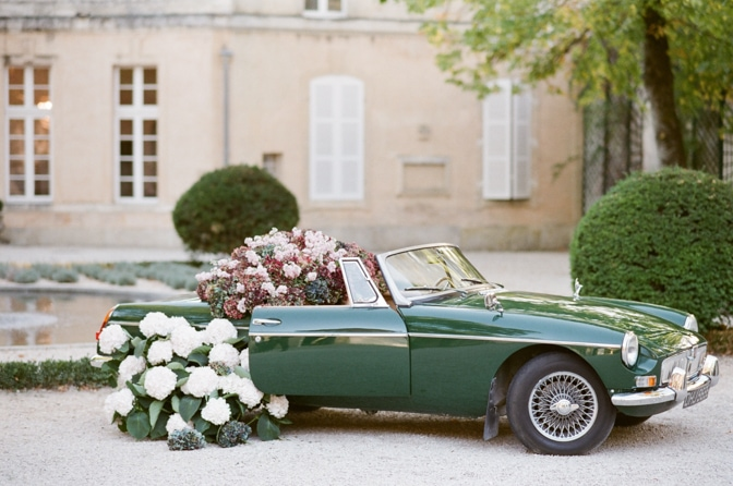 Green wedding car filled with colorful hydrangea at Chateau Martinay in Provence