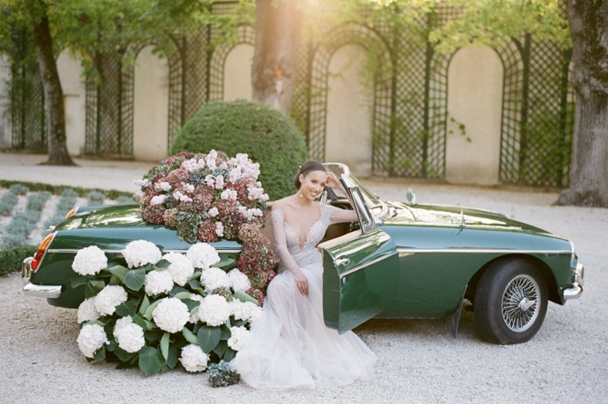 Black bride in her blush Berta Bridal gown sitting in a green car filled with colorful hydrangea at Chateau Martinay