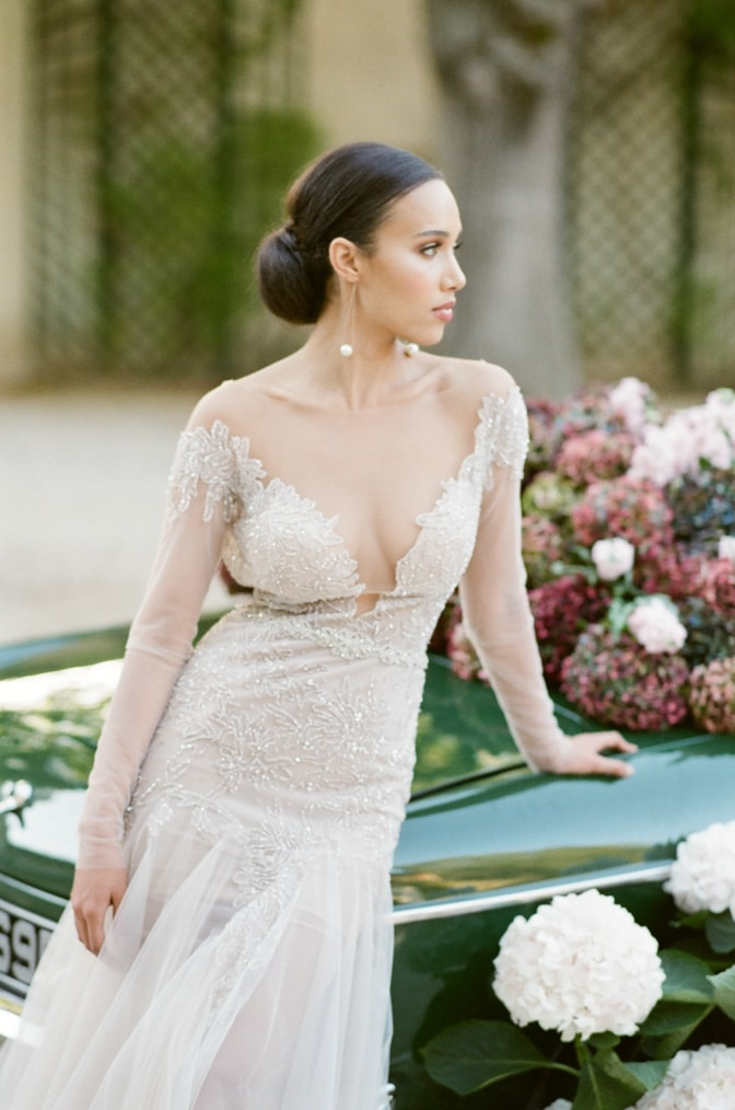 Black bride in her blush Berta Bridal gown sitting on the rear of a green car filled with colorful hydrangea at Chateau Martinay and looking away