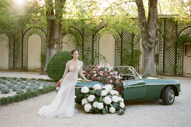 Black bride in her blush Berta Bridal gown sitting on the rear of a green car filled with colorful hydrangea at Chateau Martinay in Provence