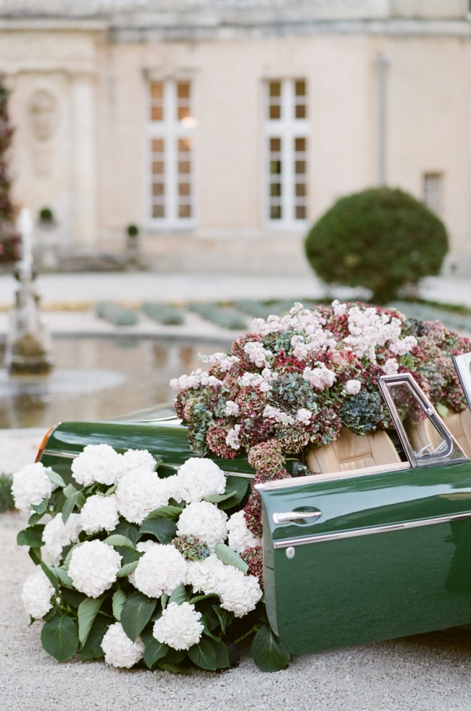 Green car overflowing with colorful hydrangea with door open at Chateau Martinay in Provence