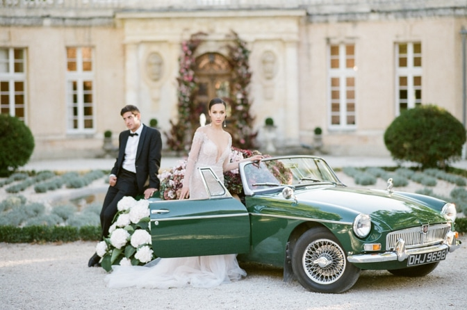 Bride and groom standing in front of a green car filled with colorful hydrangea at Chateau Martinay