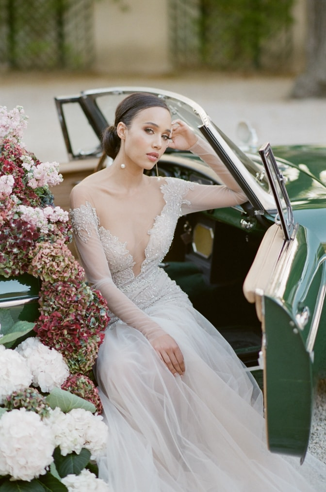 Black bride in her blush Berta wedding dress sitting in a green car filled with hydrangea with door open