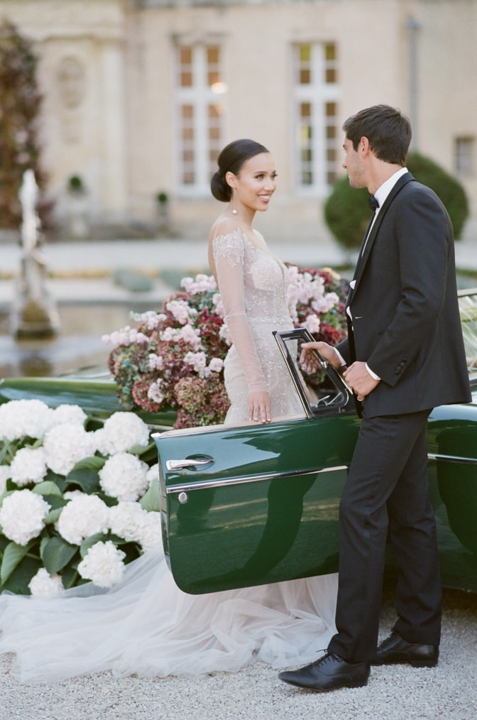 Black bride smiling at her white groom in front of a green car filled with colorful hydrangea at Chateau Martinay