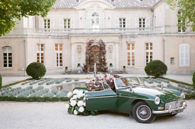 Green car overflowing with colorful hydrangea parked in front of Chateau Martinay in Provence