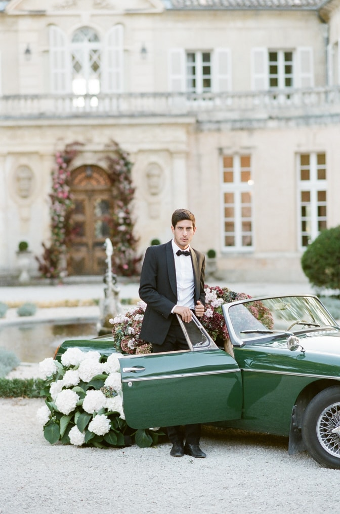Groom in his black tux exiting Chateau Martinay in a green car filled with hydrangea