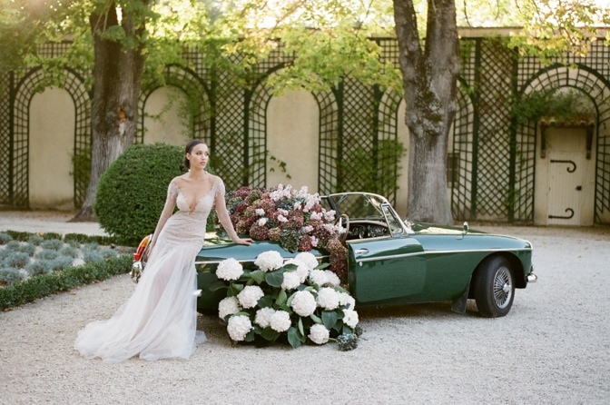 Black bride in her blush Berta Bridal gown sitting on the rear of a green car filled with colorful hydrangea at Chateau Martinay during her grand exit