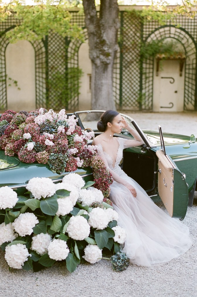 Black bride in her blush Berta Bridal gown at her grand exit in a green car filled with colorful hydrangea at Chateau Martinay in Provence