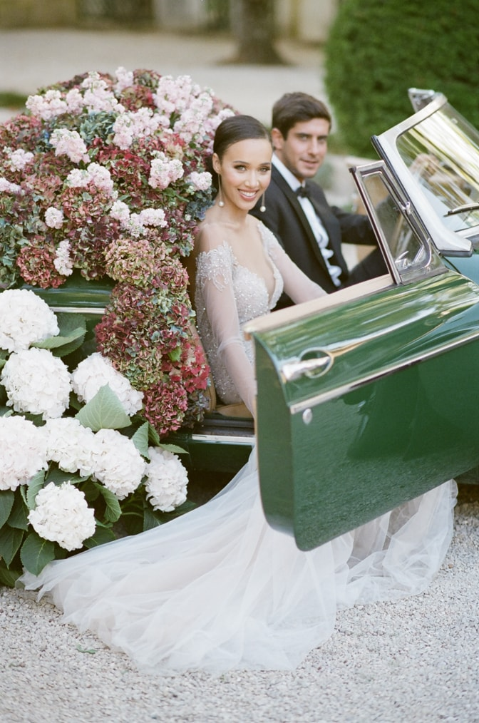 Wedding couple in green wedding car filled with colorful hydrangea at Chateau Martinay in Provence