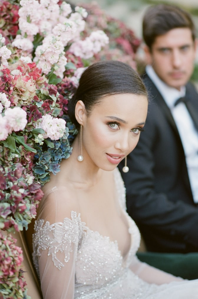 Black bride in her blush Berta Bridal gown sitting in a green car filled with hydrangea and looking into the camera