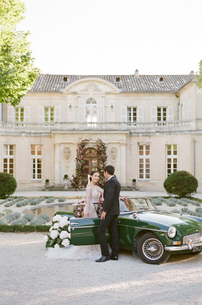 Bride and groom standing and looking at each other in front of a green car filled with hydrangea at Chateau Martinay in Provence