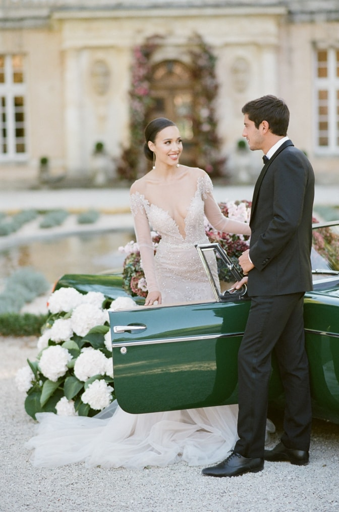 Bride looking at her groom in between a green car filled with colorful hydrangea at Chateau Martinay in Provence