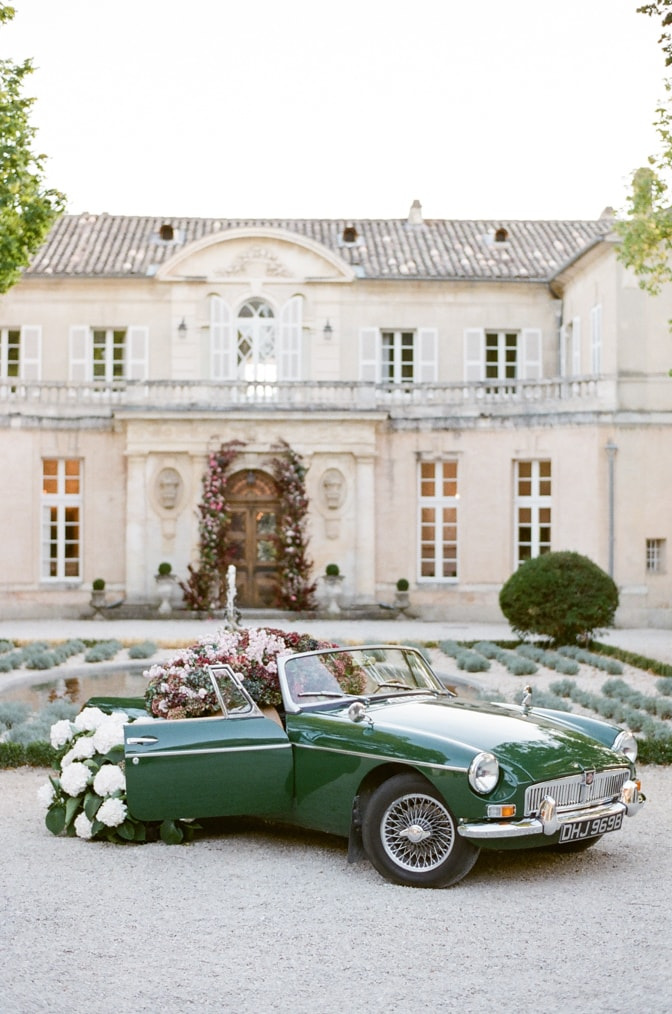 Green car filled with colorful hydrangea in front of Chateau Martinay in Provence