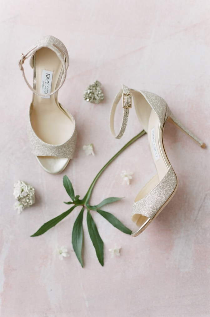 Luxury gold wedding Jimmy Choo shoes surrounded by flowers