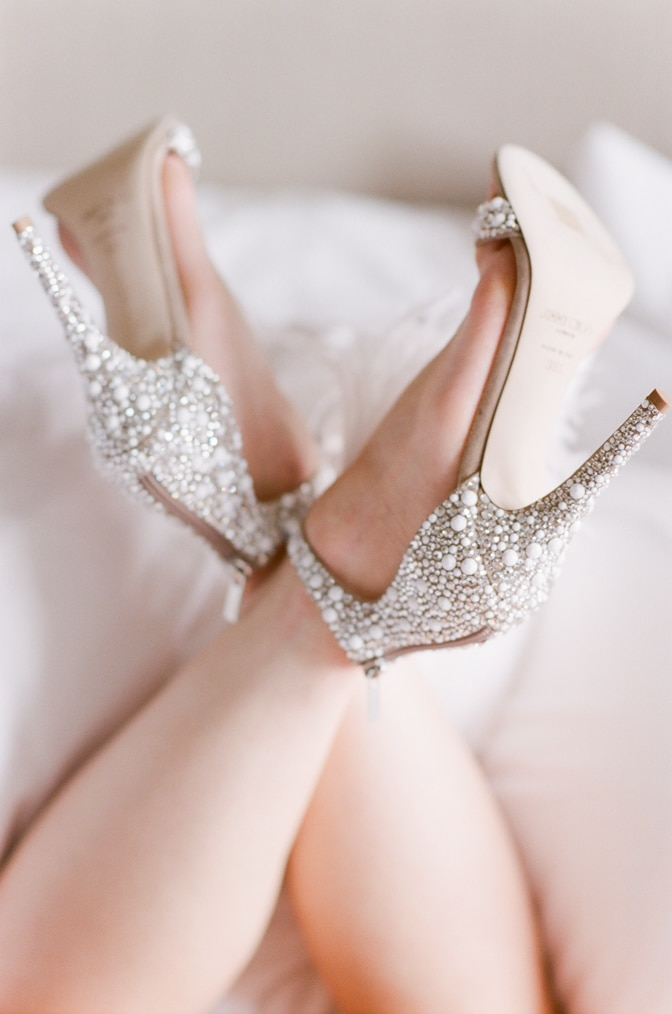 Bride wearing her luxurious Jimmy Choo shoes adorned with pearls