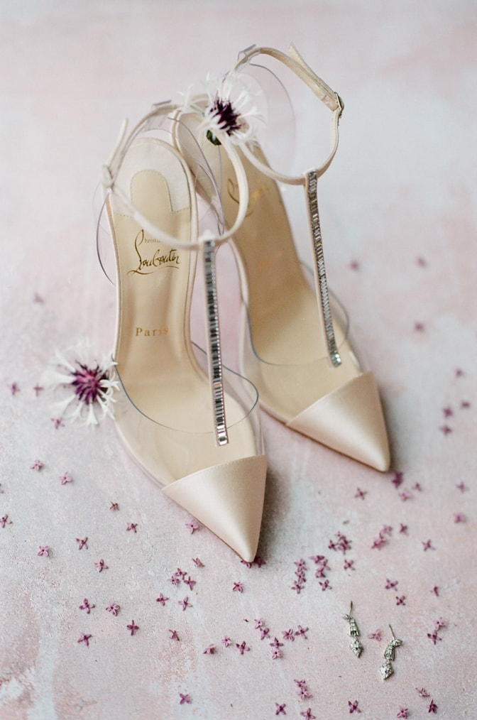 Louboutin blush glamour shoes surrounded by flowers