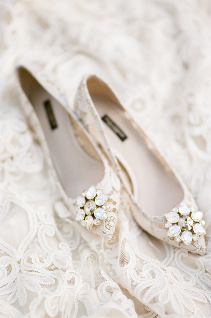 White lace Manolo Blahnik shoes with a brooch
