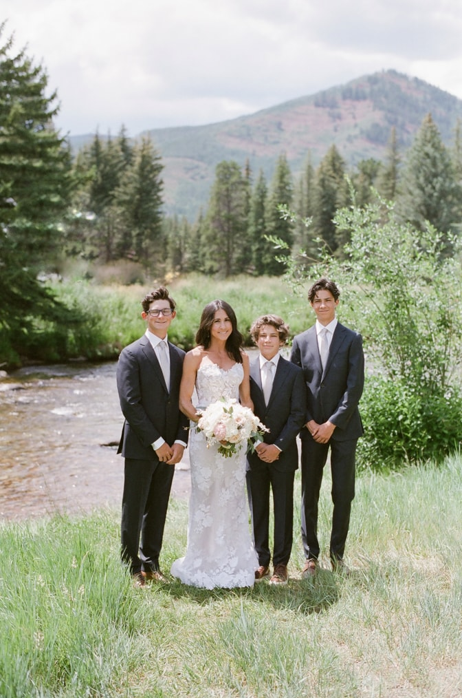 Bride in white posing with her three sons in Vail