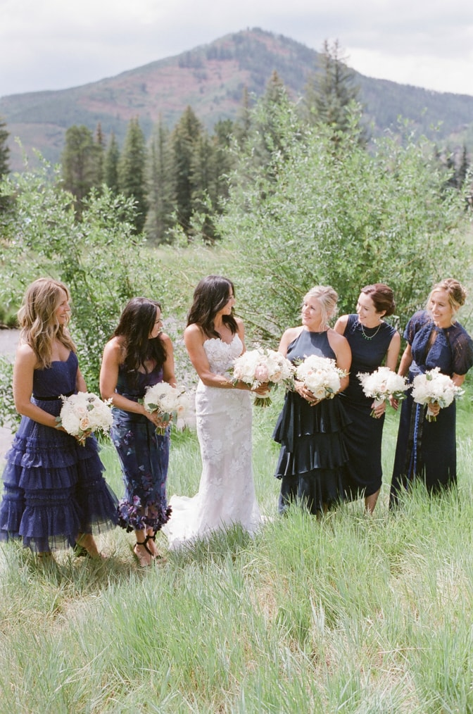 Bride & bridesmaids holding white bouquet of flowers while laughing in Vail