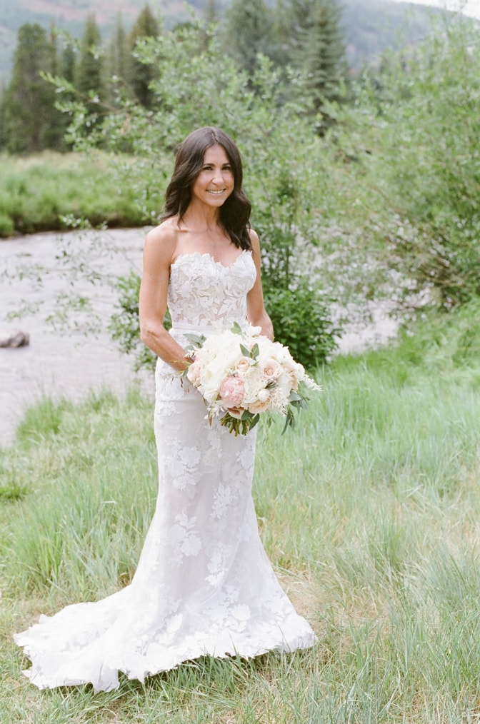 Bride in white posing in her lace Mira Zwillinger wedding dress in Vail