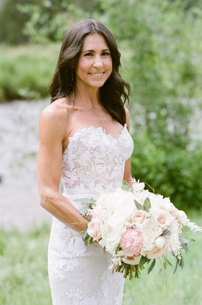 Timeless look of bride smiling wearing lace Mira Zwillinger dress holding bouquet in Vail