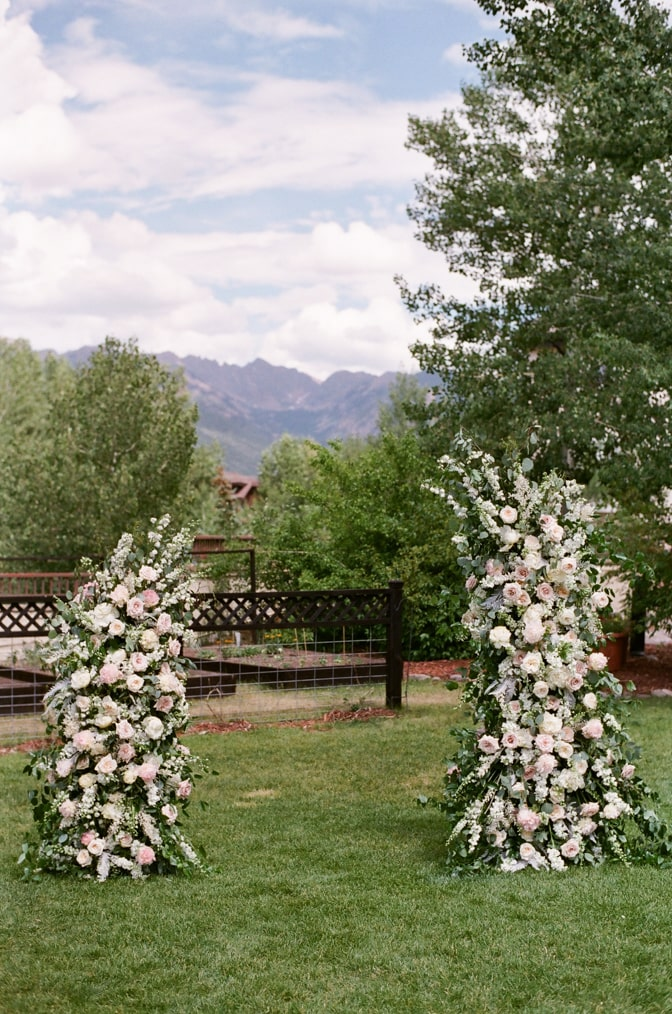 Outdoor ceremony with classic flower arch showing shades of white and pink
