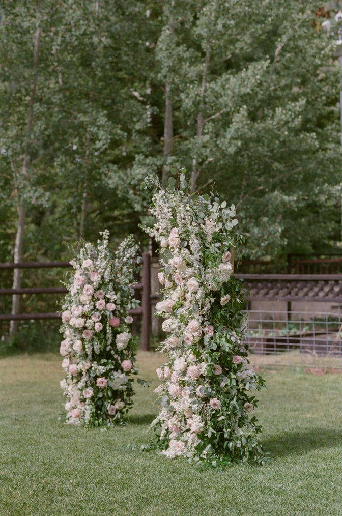 Outdoor ceremony with classic arch showing shades of white and pink at Larkspur Events and Dining in Vail