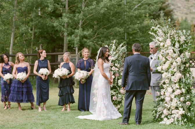 Left is bridesmaids standing holding bouquets and on right is wedding ceremony reading of vows by officiant during Vail wedding